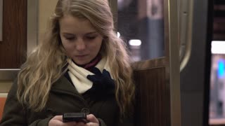 Young female sitting on metro train using her cell phone to text 4k