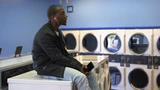 Young male dancing to music at laundromat points at camera 4k