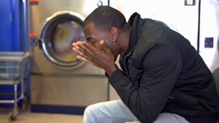 Young male frustrated and upset while sitting at laundromat 4k