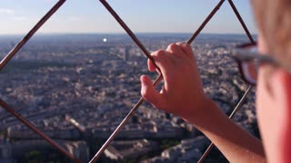 Young male holding on to fence with hand overlooking city 4k