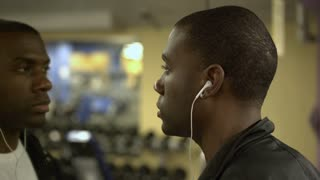 Young male listening to music at gym looking at reflection in mirror 4k