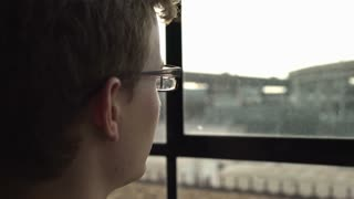Young male looking thru dusty window into busy city outside 4k