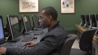 Young male sitting in computer lab smiling at screen 4k