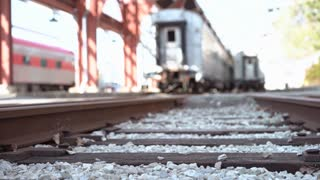 Young male walking down railroad track away from camera 4k