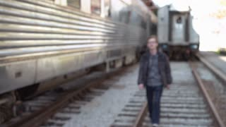 Young Male walks by camera with train in background 4k