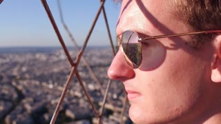 Young male wearing sunglasses overlooking city from above 4k