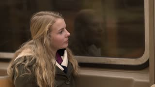 Young teenage girl looking out subway window during ride 4k