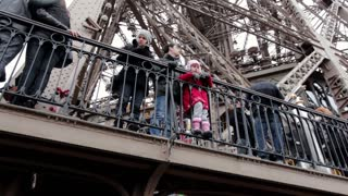 Visitors at the Eiffel Tower looking over railing
