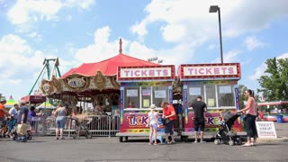 Visitors of local carnival purchasing tickets for rides 4k
