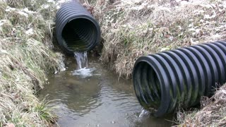 Water Draining from Two Plastic Pipes