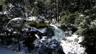 Water flowing through mountain rocks with snow