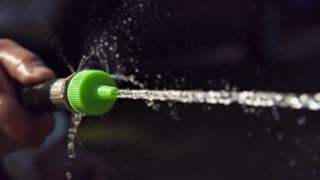 Water from garden hose sprayed out of nozzle slow motion