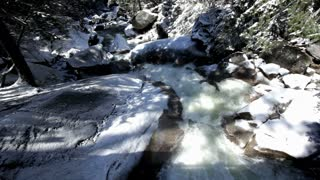 Water rushing over snow covered rocks