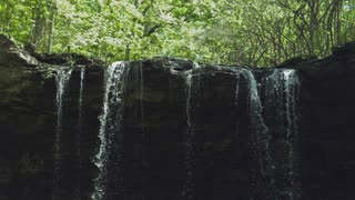 Waterfall in nature flowing over ledge slow motion