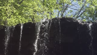Waterfall pouring over edge in super slow motion