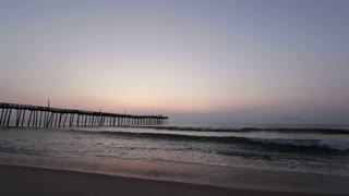 Waves on beach during sunrise pan shot