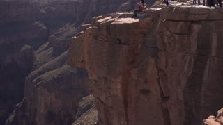 West Rim of Grand Canyon with people standing on edge tilt shot 4k