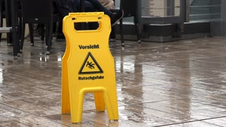 Wet floor sign on rain covered patio 4k