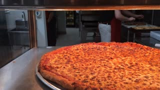 Whole cheese pizza ready at restaurant
