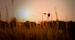 Windmill seen through wheat field 4k