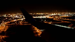 Wing View of airplane landing at Night
