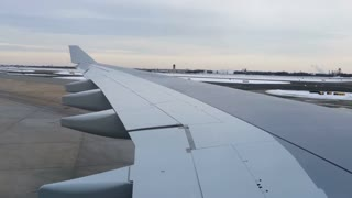 Wing view of airplane preparing to take off on runway