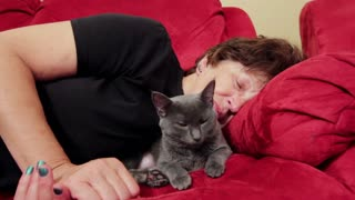 Woman and cat sleeping on couch