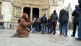 Woman asking for money from people going into Notre Dame