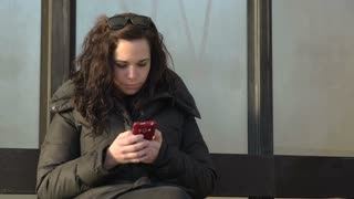 Woman at bus stop texting
