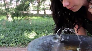 Woman getting drink of water pan shot