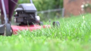 Woman in boots mowing lawn slow motion