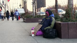 Woman sitting on side walk asking for help