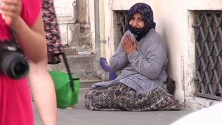 Woman sitting on street asking for money