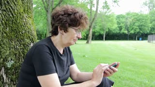 Woman texting while sitting against tree