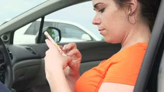 Woman using smart phone in parked car