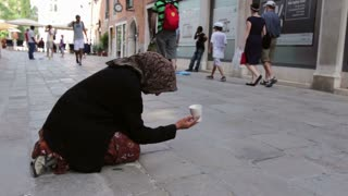 Woman with cup asking for money in Venice