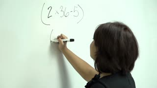 Woman working through math problem at board