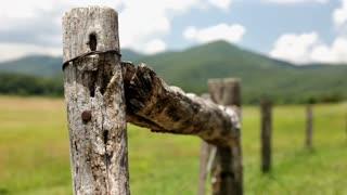 Wooden Fence in field and cloudy mountains
