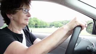 Worried woman driving car seen from passenger side