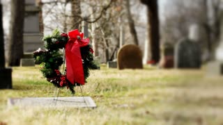Wreath on grave in graveyard