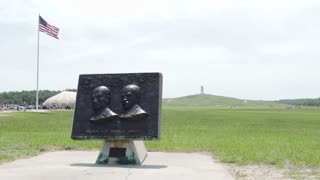 Wright Brothers memorial with field and flag in background