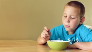 Young Boy eating a bowl of cereal