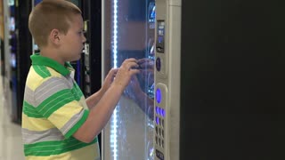 Young boy getting snack from vending machine