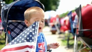 Young Boy in Stroller waving american flag