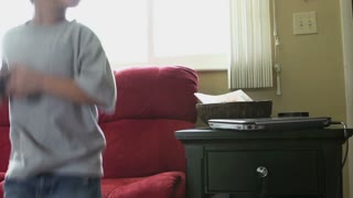 Young boy jumps onto couch while playing game