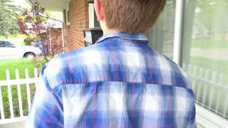 Young boy knocks on front door then looks through window 4k