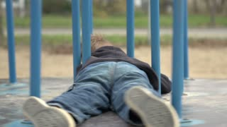 Young boy laying on merry go round