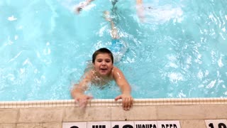 Young boy playing and splashing in swimming pool 4k