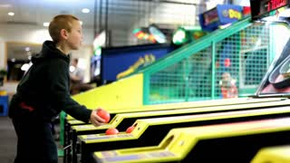 Young Boy playing Skee Ball