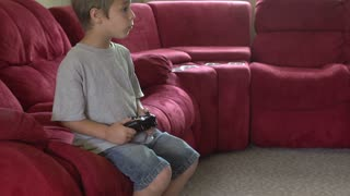 Young boy playing video games stops
